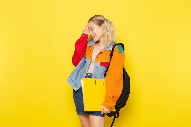 単に黄色の笑顔でポーズをとって現代の服の若い女子学生