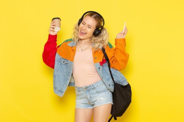 Студентка молодая в современной одежде слушает музыку с кофе на желтом