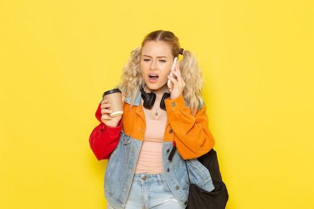 黄色のコーヒーを保持している電話で話している現代の服の若い女子学生