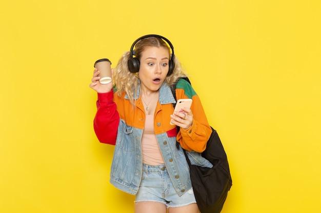 黄色の電話を使用して現代の服の若い女子学生