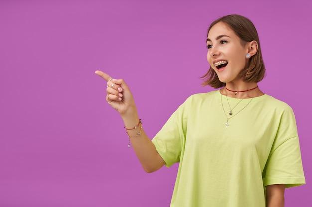 紫色の壁の上のコピースペースで笑って左に指を向けている女子学生、若い女性。兆候を示しています。緑のtシャツ、歯列矯正器、ブレスレット、指輪を身に着けている