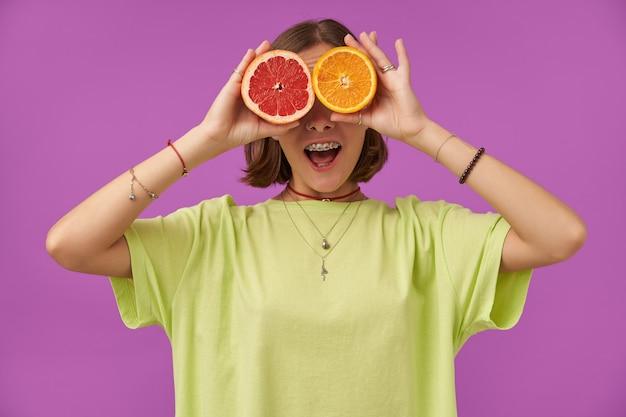 여성 학생, 큰 미소를 가진 젊은 아가씨, 그녀의 눈 위에 자몽과 오렌지를 들고. 보라색 벽 위에 서 있습니다. 녹색 티셔츠, 치아 교정기, 팔찌 및 목걸이 착용
