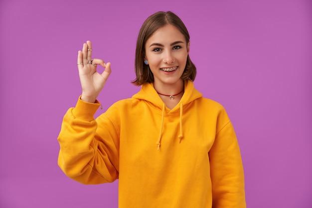 Studentessa, giovane donna con i capelli corti castani. mostra un segno che va tutto bene. indossare una felpa arancione, parentesi graffe e anelli per i denti