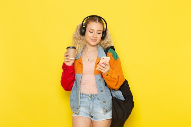 Female student young in modern clothes holding coffee and phone on yellow