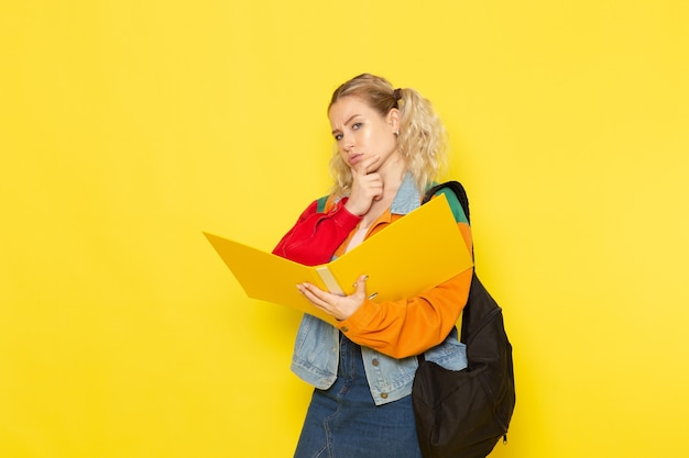 Female student young in modern clothes holding files thinking on yellow