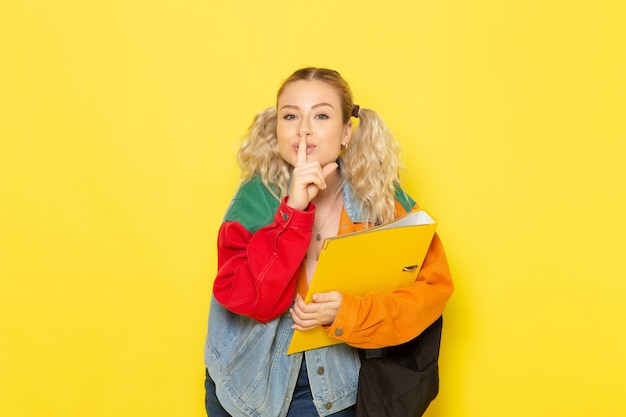 Studentessa giovane in abiti moderni solo tenendo lezioni shoing silenzio segno giallo