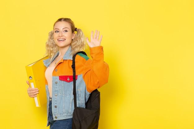 Studentessa giovane in abiti moderni semplicemente in posa con il sorriso che tiene il file sventolando sul giallo