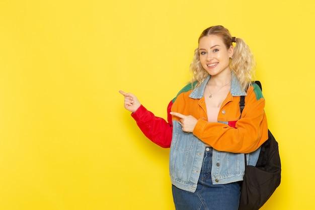 Studentessa giovane in abiti moderni semplicemente in posa con il sorriso sul giallo