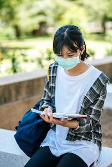 階段でマスクと本を身に着けている女子学生。