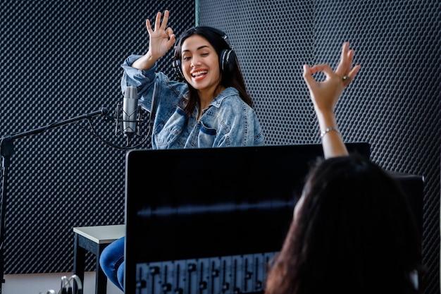 若いアジアの女性ボーカリストの前景で録音するためのソフトウェアのコンピューターモニターの女性スタジオ技術者プロのスタジオでマイクの前で歌を録音するヘッドフォンを着用