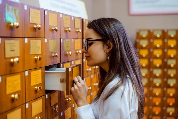 Женский студнет ищет нужную книгу в картотеке библиотеки.