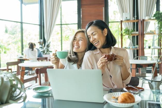 Девушка изучает местную кофейню. две женщины обсуждают бизнес-проекты в кафе за чашкой кофе. запуск, идеи и концепция мозгового штурма. улыбающиеся друзья с горячим напитком, используя ноутбук в кафе