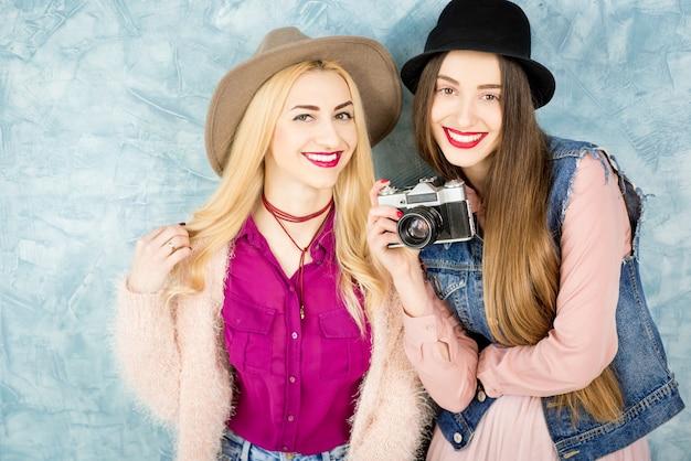 파란색 벽 배경에서 사진 카메라로 즐거운 시간을 보내는 세련된 여성 친구들