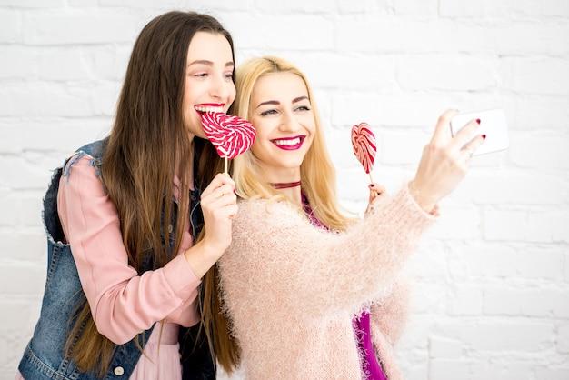 白い壁の背景に赤いキャンディーで自分撮り写真を作る女性のスタイリッシュな友達