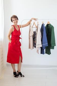 옷걸이와 선반 근처 여성 스타일리스트. 쇼핑, 의류 디자이너 및 소비 개념.