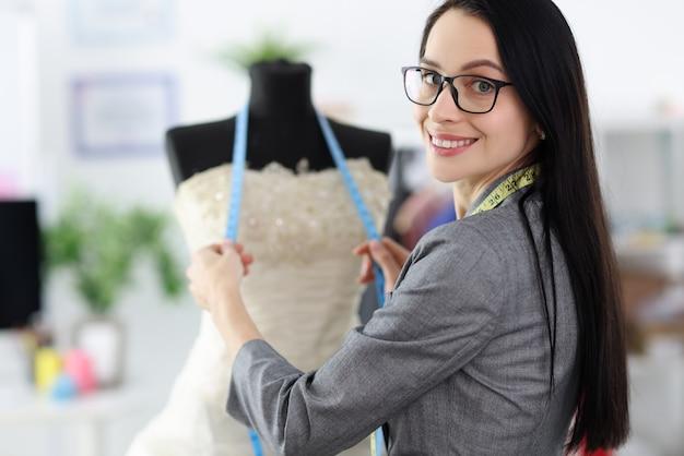 Женский стилист стоит рядом с манекеном в свадебном платье.