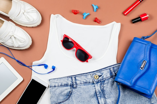 Female summer clothing collection, relaxed casual style. white top, blue jeans, loafers, red and blue accessories, gadgets.