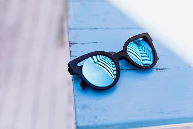 Женские солнцезащитные очки, лежа на синем деревянном столе.