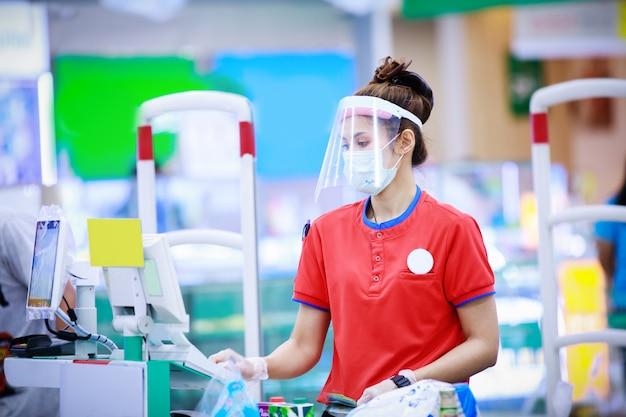 スーパーマーケットで働く医療用防護マスクと顔面シールドの女性のスーパーマーケットのレジ係。コロナウイルスの概念