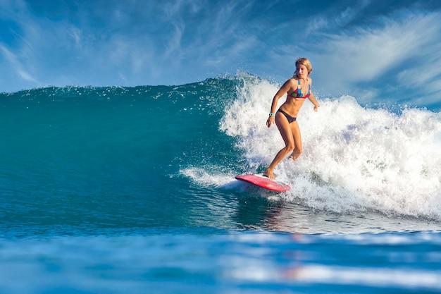 Женский серфер на синей волне в солнечный день