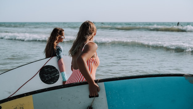 서핑보드를 들고 바다로 걸어가는 여성 서퍼들