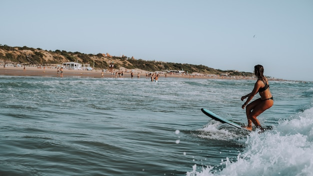 Female surfing on small waves