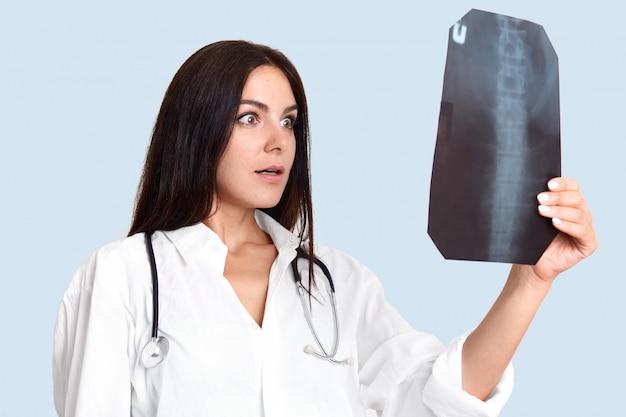 Female surgeon examines x ray