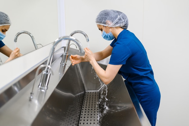 マスクをした女性外科医が手を洗い、手術の準備をする