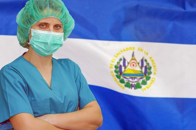 Female surgeon in mask and hat looks at the camera on the background of the el salvador flag