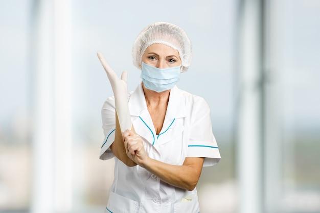 Женский хирург надевает перчатку. врач женской медицины в защитной маске и кепке, надевая белую защитную перчатку, размытую.