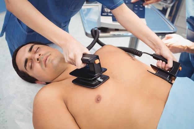 Женщина хирург реанимирует больного без сознания с помощью дефибриллятора