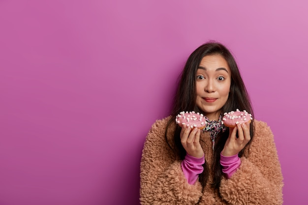 여성 달콤한 치아는 맛있는 유약 색의 도넛을 들고 설탕 중독이 있으며 지금 맛있는 디저트를 먹고 싶어합니다.