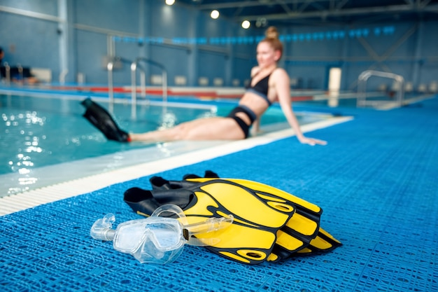 Female swimmer in flippers poses at the poolside, water surface