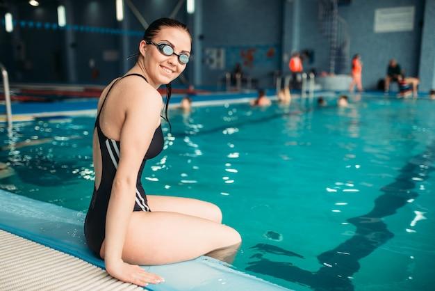 スイミングプールの端に座っているゴーグルの女子水泳選手。トレーニング、ウォータースポーツの水着の女性