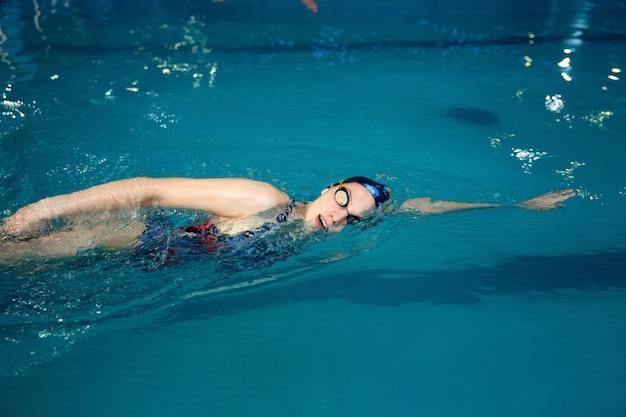 Пловец в купальнике, кепке и очках плавает на спине в бассейне