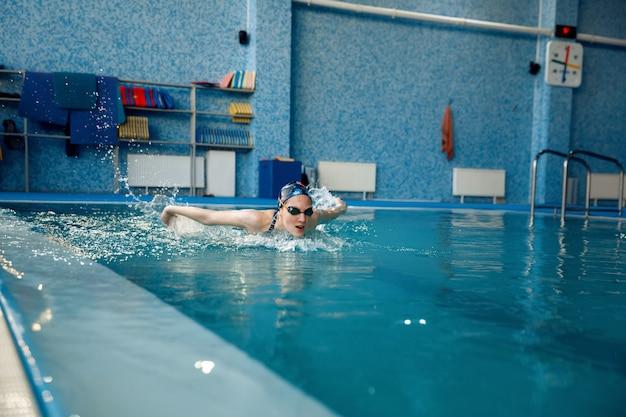Пловец в купальнике, кепке и очках плавает бабочка в бассейне