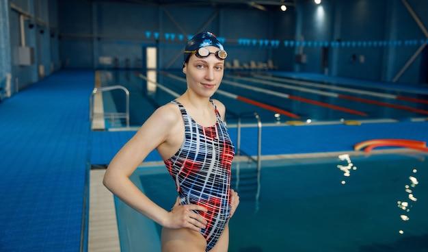 Пловец в купальнике, шапочке и очках позирует в бассейне