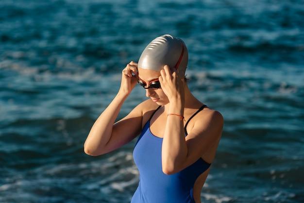 Nuotatore femminile con cappuccio e occhiali da nuoto