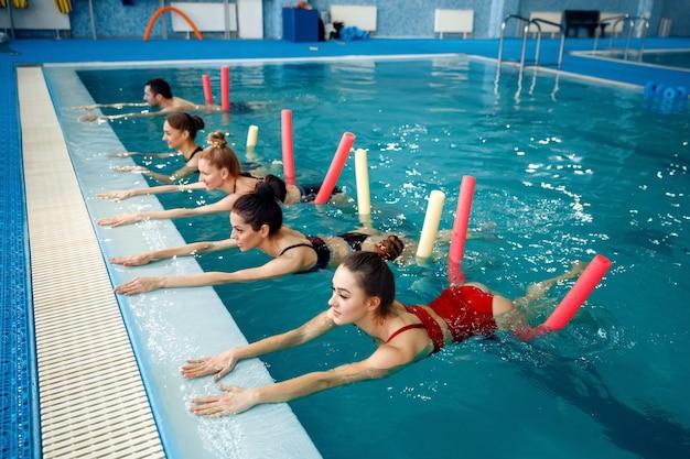 Группа пловцов, занятия аквааэробикой в бассейне. женщины в воде, спортивное плавание, фитнес-тренировка