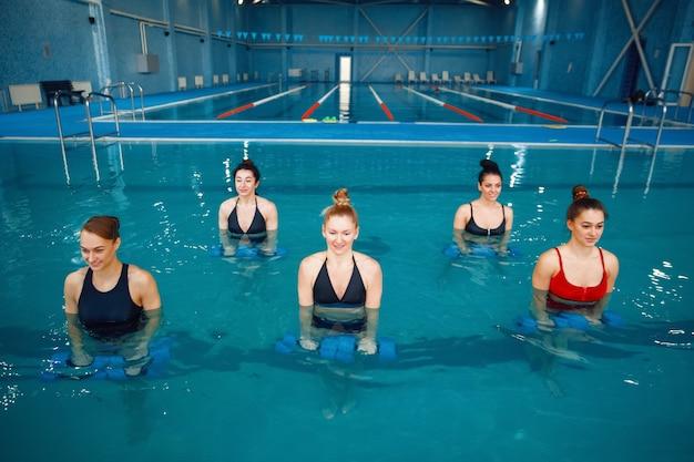女性スイマーグループ、アクアビクス、プールでダンベルを使ったトレーニング