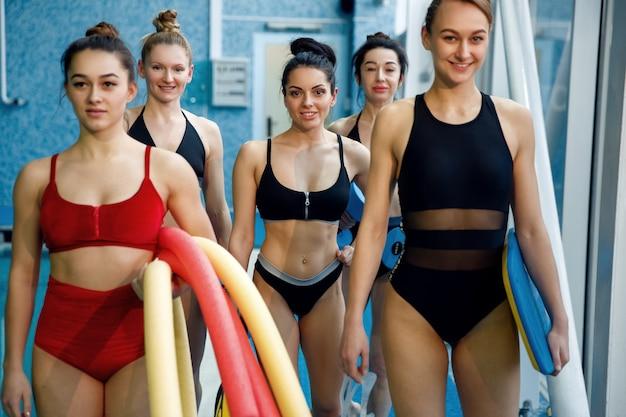 アクアビクストレーニングの後、プールサイドで女子水泳選手が集まります。水の近くの女性、プールでのスポーツ水泳フィットネストレーニング