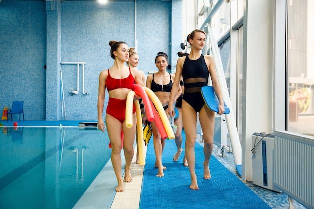 アクアビクストレーニング後のプールサイドでの女子水泳選手グループ
