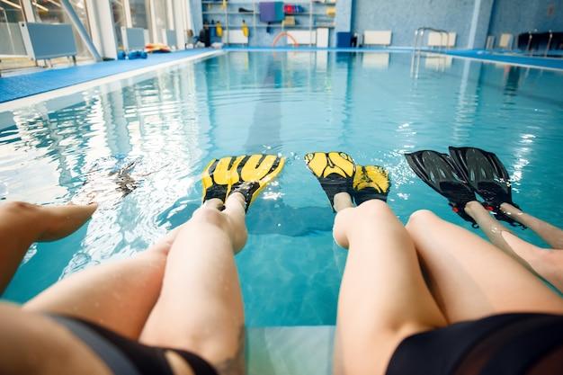 足ひれをつけたプールサイドで女子水泳選手が集まります。水の近くの女性、プールでのスポーツ水中水泳トレーニング