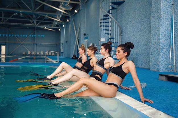 女子水泳選手はプールサイドで足ひれに集まります。水の近くの女性、プールでのスポーツ水中水泳トレーニング