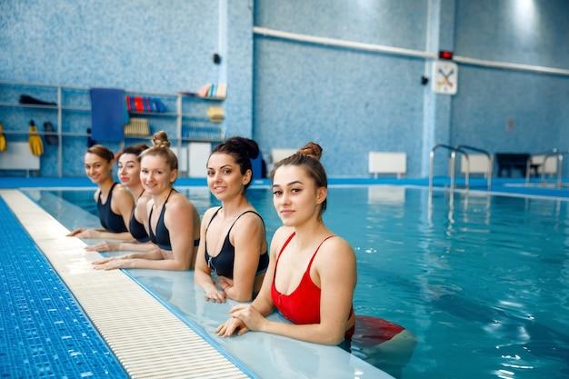 女子水泳選手グループがプールサイドでポーズをとる。女性は水中でのトレーニング、スポーツ水泳、プールでのフィットネストレーニングに適しています