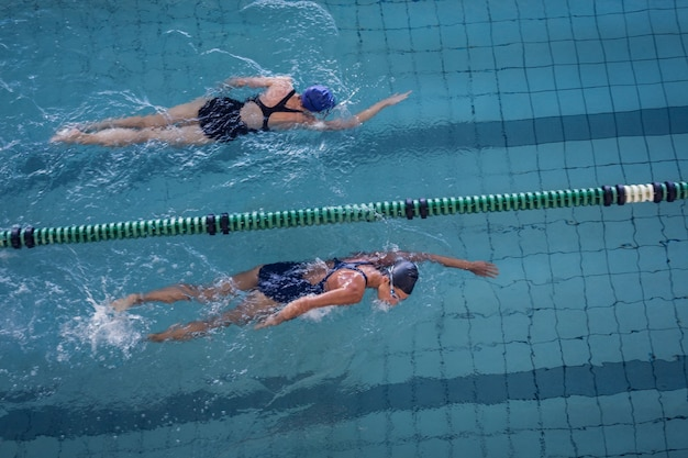 Женщины-пловцы, мчащиеся в бассейне
