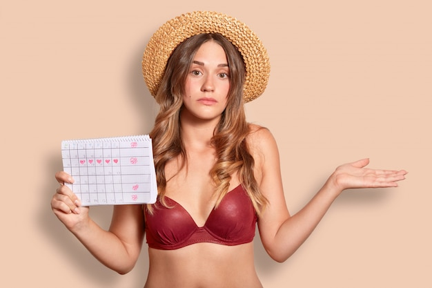 Female in swimsuit, shruggs shoulders, wears straw hat and bikini, holds period calendar