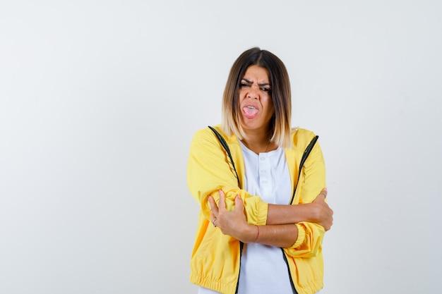 Donna in t-shirt, giacca in piedi con le braccia incrociate, lingua sporgente e sguardo dispettoso, vista frontale.