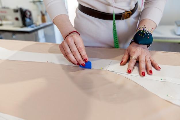Женский портной руки с тканью, узором и иглой в мастерской