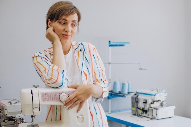 Женский портной, держащий швейную машину